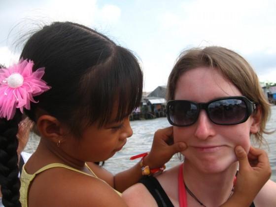 vietnamesiches Mädchen zieht Martina die Backen lang