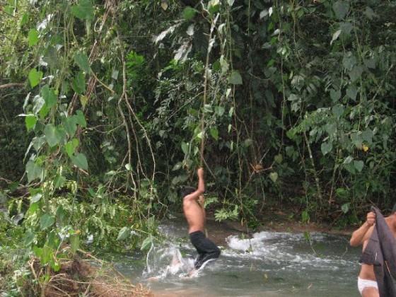 Junge schwingt an einer Liane über den Fluss