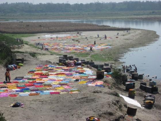 Bunte Wäsche liegt zum Trocknen am Ufer aus, nachdem sie in dem dreckigen Fluss gewaschen wurde