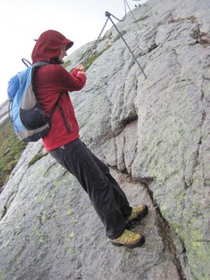 Martina lässt sich an einer Kette den steilen, rutschigen Fels runter